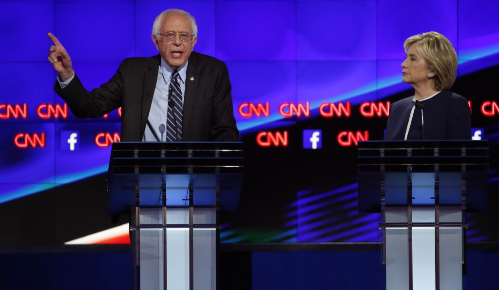 Democratic presidential candidate Senator Bernie Sanders speaks as former Secretary of State Hillary Clinton looks on during the first official Democratic candidates debate. Photo by Lucy Nicholson/Reuters