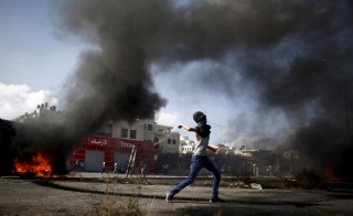 A Palestinian protester uses a sling to hurl stones towards Israeli troops during clashes near the Jewish settlement of Beit El, near the West Bank city of Ramallah October 14, 2015. Seven Israelis and 31 Palestinians, including children and assailants, have been killed in two weeks of bloodshed in Israel, Jerusalem and the occupied West Bank. The violence has been partly triggered by Palestinians' anger over what they see as increased Jewish encroachment on Jerusalem's Al-Aqsa mosque compound, also revered by Jews as the site of two destroyed Jewish temples.  REUTERS/Mohamad Torokman - RTS4GX1