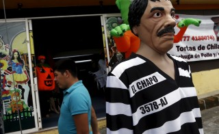 """A man walks past a costume of Joaquin """"El Chapo"""" Guzman on display in the Mexican city of Cuernavaca on Oct. 14. The costume is expected to be a hot seller. Photo by Henry Romero/Reuters"""