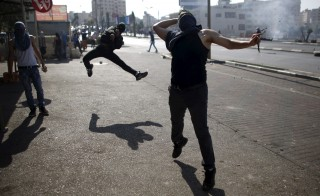 Palestinian protesters hurl stones towards Israeli troops during clashes near the Jewish settlement of Bet El, near the West Bank city of Ramallah October 16, 2015. The unrest that has engulfed Jerusalem and the occupied West Bank, the most serious in years, has claimed the lives of 35 Palestinians and seven Israelis. The tension has been triggered in part by Palestinians' anger over what they see as increased Jewish encroachment on Jerusalem's al-Aqsa mosque compound, which is also revered by Jews as the location of two destroyed biblical Jewish temples. REUTERS/Mohamad Torokman - RTS4RSS