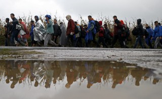 Migrants walk along a road after crossing the border with Serbia in Babska, Croatia, on Oct. 19. The Balkans struggled with a growing backlog of migrants on Monday after Hungary sealed its southern border and Slovenia tried to impose a limit, leaving thousands stranded at the border. Photo by Dado Ruvic/Reuters