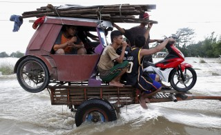 Residents carry gear in a tractor trailer along a flooded highway in Zaragoza, Nueva Ecija in northern Philippines on Oct. 20, after the province was hit by Typhoon Koppu. Photo by Erik De Castro/Reuters