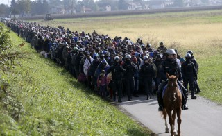 A mounted policeman leads a group of migrants near Dobova, Slovenia October 20, 2015. Slovenia's parliament is expected to approve changes to its laws later on Tuesday to enable the army to help police guard the border, as thousands of migrants flooded into the country from Croatia after Hungary sealed off its border. REUTERS/Srdjan Zivulovic TPX IMAGES OF THE DAY   - RTS584D