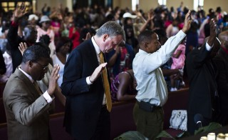 New York City mayoral candidate Bill de Blasio (second from left) prays during a church service at Philadelphia Seventh-day Adventist Church in the Bronx, in 2013. Ben Carson, who is a practicing member of the church, is bringing more attention to the denomination. Photo by Eduardo Munoz/Reuters