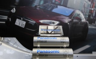 Panasonic Corp's lithium-ion batteries, which are part of Tesla Motor Inc's Model S and Model X battery packs, are displayed in front of a poster of a Tesla Model S during a news conference at the Panasonic Center in Tokyo, ahead of the 2013 Tokyo Motor Show, November 19, 2013. The Tokyo Motor Show will be held from November 22 to December 1. REUTERS/Yuya Shino (JAPAN - Tags: TRANSPORT BUSINESS) - RTX15JFC