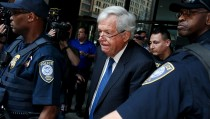 Former Speaker Dennis Hastert is surrounded by officers as he leaves federal court, regarding a hush-money case. Hastert, 73, told a judge Thursday that he intends to plead guilty for trying to evade detection of $3.5 million in payments he had promised to someone from his hometown of Yorkville, Illinois, to conceal past misconduct. Photo by Jim Young/Reuters