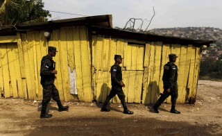 Members of the Military Police for Public Order (PMOP) patrol the impoverished Flor del Campo neighbourhood in Tegucigalpa, Honduras, April 29, 2015. Since taking office in January 2014, Honduras' President Juan Orlando Hernandez has delegated the intelligence and counternarcotics operations to the military, creating the Military Police for Public Order, a new force that patrols violent neighbourhoods, public schools and playgrounds to curb violence, amidst growing claims of human rights abuses. Picture taken April 29, 2015. REUTERS/Jorge Cabrera - RTX1IMAG