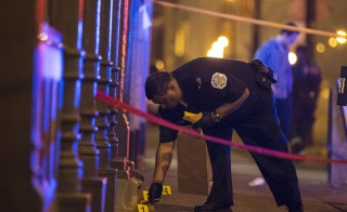 A Chicago police officer collects evidence at a crime scene where a man was shot in Chicago, Ill., on July 5, 2015. President Barack Obama is expected to address violent crime amid a rise in homicides in several major U.S. cities. Photo by Jim Young/Reuters