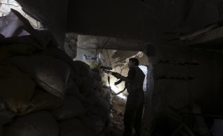 A fighter from the Free Syrian Army's Al Rahman legion takes up a position behind sandbags piled up on the frontline against the forces of Syria's President Bashar al-Assad in Jobar, a suburb of Damascus, Syria July 27, 2015. REUTERS/Bassam Khabieh - RTX1M0D7