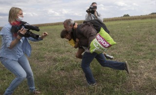 A migrant runs with a child before tripping on TV camerawoman Petra Laszlo (L) and falling as he tries to escape from a collection point in Roszke, Hungary on Sept. 8, 2015. Laszlo, a camerawoman for a private television channel in Hungary, said she plans to take legal action against one of migrants she tripped and Facebook. Photo by Marko Djurica