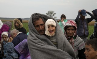 Migrants stand in a field as they wait for buses to take them to shelters after they crossed the border from Serbia, near Tovarnik, Croatia, on Sept. 24, 2015. Photo by Marko Djurica/Reuters