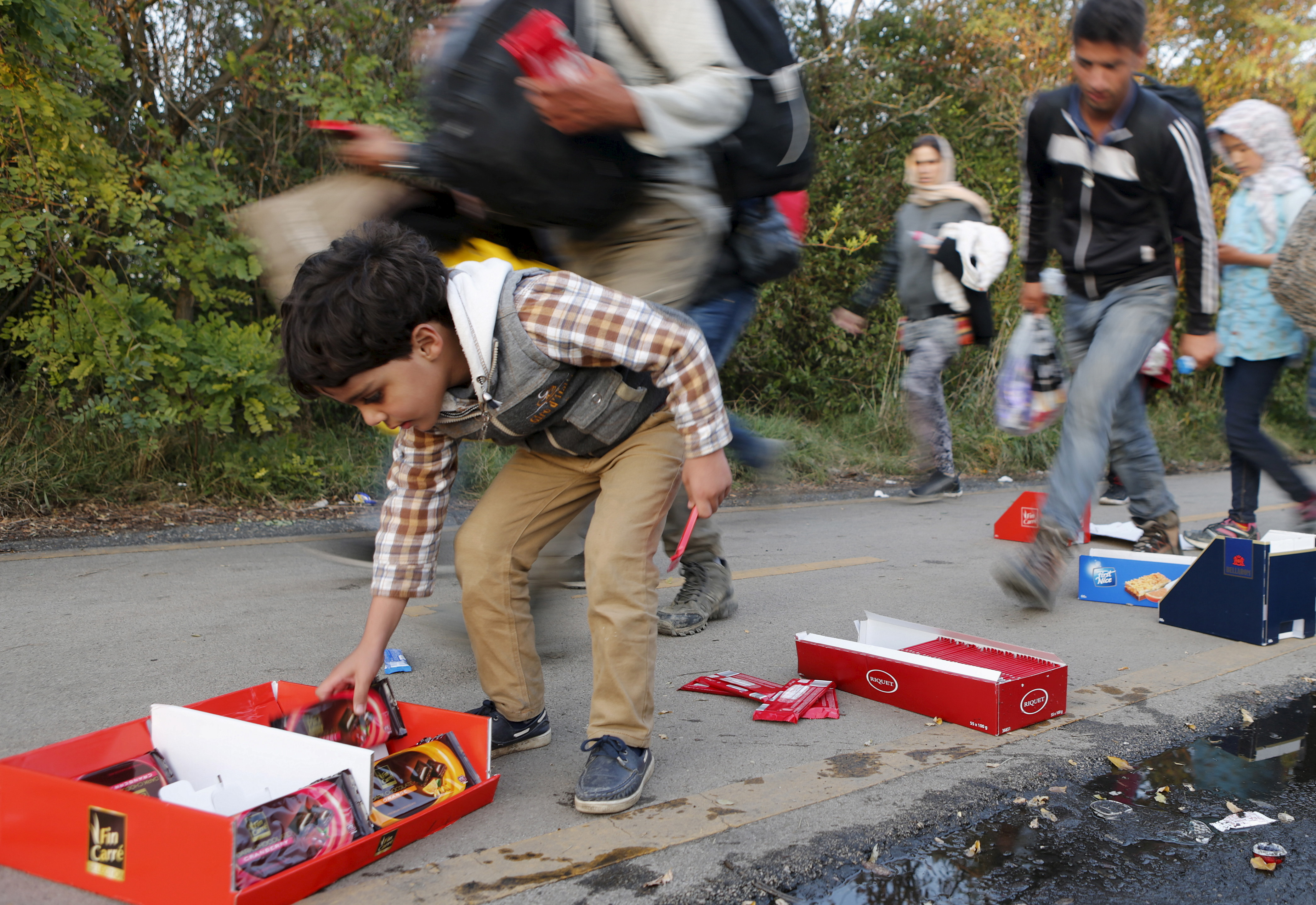 A child reaches for candy that had been placed by the road on the way to Austria, in Hegyeshalom, Hungary, on Sept. 27, 2015. Tens of thousands of migrants, most of them fleeing war and hardship in Syria, are trying to reach Western Europe. Photo by Heinz-Peter Bader/Reuters