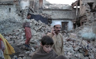 Residents walk past the rubble of a house after it was damaged by an earthquake in Mingora, Swat, Pakistan, October 26, 2015. A powerful earthquake struck a remote area of Afghanistan on Monday, shaking the capital Kabul with shockwaves felt in northern India and in Pakistan, where hundreds of people ran out of buildings as the ground rolled beneath them. The death toll could climb because communications were down in much of the rugged Hindu Kush mountain range area where the quake was centered. REUTERS/Hazrat Ali Bacha? - RTX1TAG1