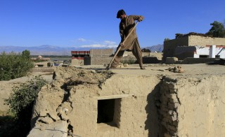 A man clears off his damaged roof after an earthquake in Behsud district of Jalalabad province, Afghanistan on Oct. 27.  Rescue workers on Tuesday rushed to deliver aid to victims of a massive earthquake that hit northern Afghanistan and Pakistan. Photo by Parwiz/Reuters