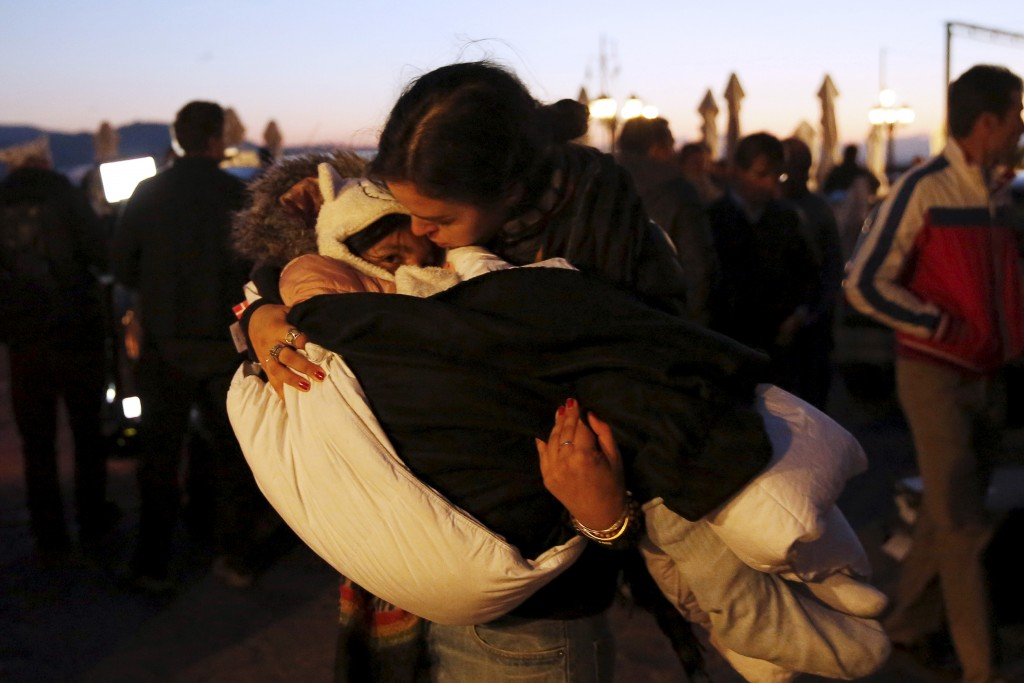 A volunteer carries a rescued child after a boat carrying more than 200 refugees and migrants sunk while crossing part of the Aegean sea from Turkey, on the Greek island of Lesbos, Oct. 28, 2015. Since the Nov. 13 attacks on Paris, several U.S. governors have made statements vowing to keep refugees from entering their states. Photo by Giorgos Moutafis/Reuters