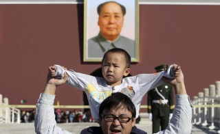 A boy sits on his father's shoulders as they pose for a photograph in front of the giant portrait of late Chinese chairman Mao Zedong on the Tiananmen Gate, in Beijing, China, October 2, 2011. China will ease family planning restrictions to allow all couples to have two children after decades of the strict one-child policy, the ruling Communist Party said on October 29, 2015, a move aimed at alleviating demographic strains on the economy. Picture taken October 2, 2011. REUTERS/Stringer   CHINA OUT. NO COMMERCIAL OR EDITORIAL SALES IN CHINA - RTX1TSTQ
