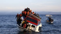 A Greek fishing boat (R) sails next to a half-sunken catamaran carrying around 150 refugees, most of them Syrians arriving after crossing part of the Aegean sea from Turkey, on the Greek island of Lesbos, October 30, 2015. There were no casaulties amongst the refugees who were travelling on the catamaran, according to a Reuters witness. The death toll from drownings at sea has mounted recently as weather in the Aegean has taken a turn for the worse, turning wind-whipped sea corridors into deadly passages for thousands of refugees crossing from Turkey to Greece.  REUTERS/Giorgos Moutafis - RTX1TXDK