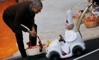 U.S. President Barack Obama receives a child dressed as Pope Francis on the South Lawn of the White House during a Halloween trick-or-treating celebration in Washington October 30, 2015. Invitees included local children and the children of military families, according to the White House. REUTERS/Carlos Barria - RTX1U1G3