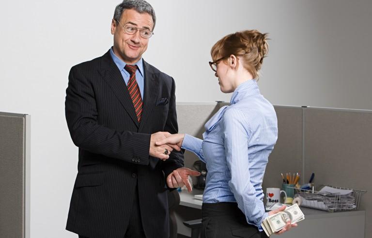 Businesswoman holding money behind her back