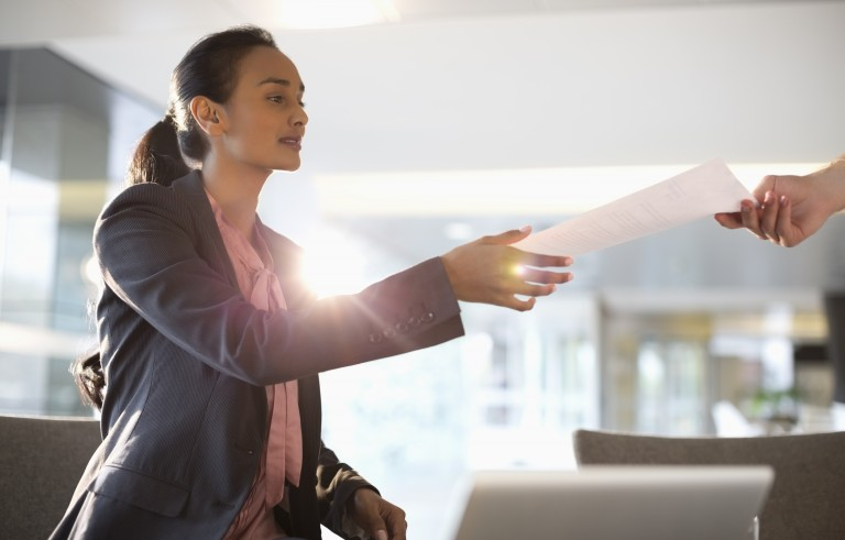 Businesswoman reaching for paperwork