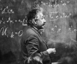 circa 1931:  German-born physicist Albert Einstein (1879 - 1955)  standing beside a blackboard with chalk-marked mathematical calculations written across it.  (Photo by Hulton Archive/Getty Images)