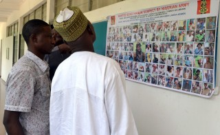 People look at a poster in Maiduguri on Oct. 28 displaying Boko Haram suspects declared wanted by the Nigerian army. Photo by Stringer/AFP/Getty Images