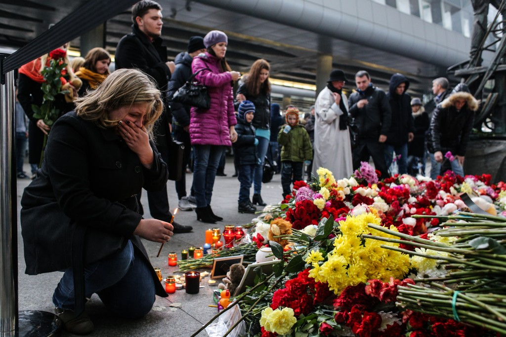 A woman holds a candle at a memorial for the victims of Airbus A321 crash at the Pulkovo Airport on November 1, 2015 in St. Petersburg, Russia. Photo by Alexander Aksakov/Getty Images.