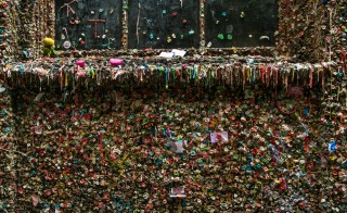 "SEATTLE, WA - NOVEMBER 5:  Tourists enjoy sticking wads of gum to surrounding walls and taking selfies at Seattle's famed ""Gum Wall"" on November 5, 2015, in Seattle, Washington. Located in an alley below Pike Place Market, the gum wall will be steam cleaned next week after accumulating 20 years of chewing gum. (Photo by George Rose/Getty Images)"