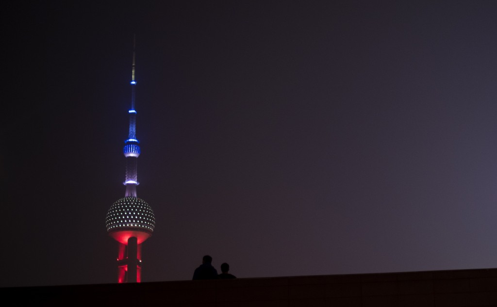 The Oriental Pearl TV Tower (L), in the Lujiazui Financial District in Pudong, is lit in red, white and blue, resembling the colors of the French flag, in Shanghai on November 14, 2015, as the Chinese expressed their solidarity with France following a spate of deadly coordinated attacks in Paris late on November 13. Photo by Johannes Eisele/AFP/Getty Images