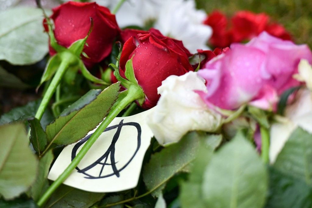 Flowers and a peace sign in the shape of the Parisian landmark the Eiffel Tower, are seen outside the French embassy in Minsk on November 14, 2015, a day after deadly attacks in Paris. Photo by Maxim Malinovsky/AFP/Getty Images