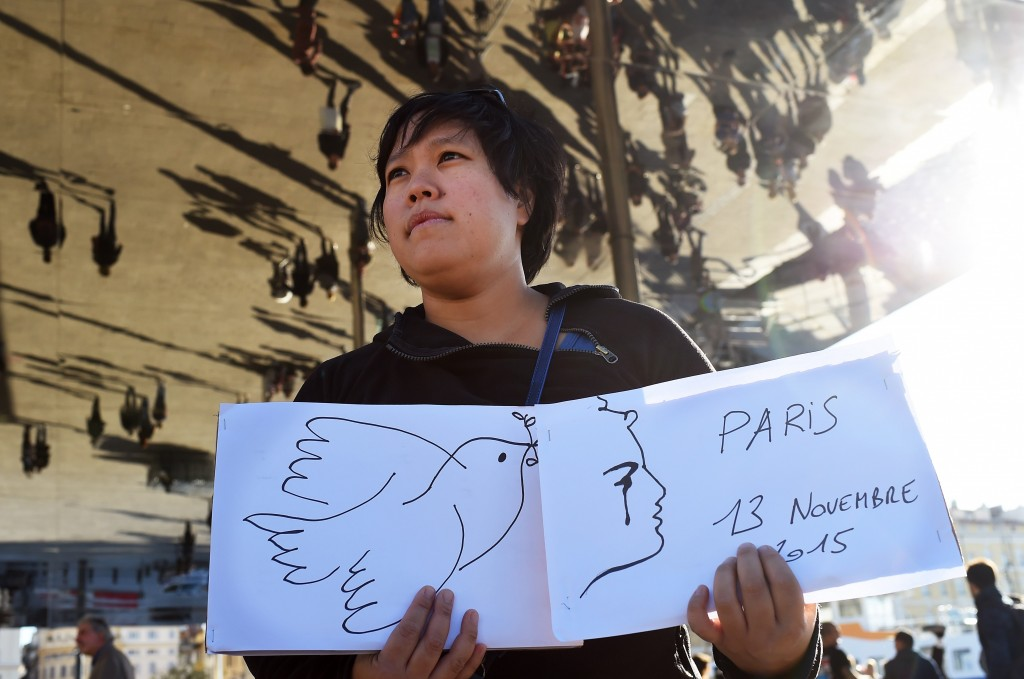 A woman holds signs at the harbor in Marseille, on November 14, 2015, the day after a total of six separate attacks, which killed at least 128 people in Paris, one targeting the national stadium where the French and German national football teams were playing a friendly.  Photo by    Anne-Christine Poujoulat/AFP/Getty Images