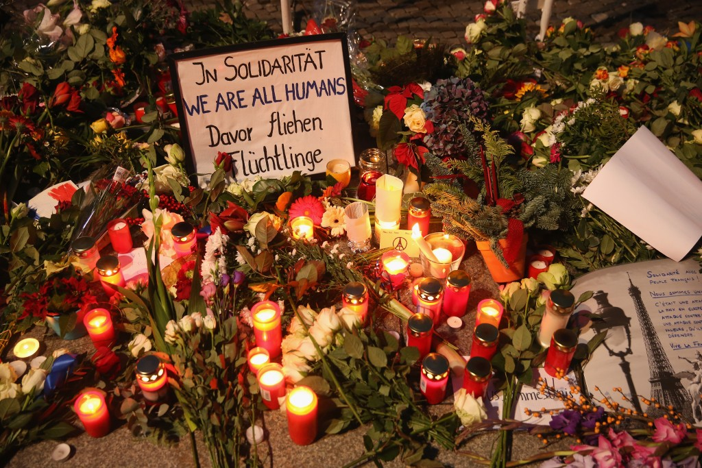 Hand-written messages lie among flowers and candles left by mourners at the gate of the French Embassy following the recent terror attacks in Paris on November 14, 2015 in Berlin, Germany. Hundreds of people came throughout the day to lay flowers, candles and messages of condolence to mourn the victims of attacks last night in Paris. Photo by Sean Gallup/Getty Images