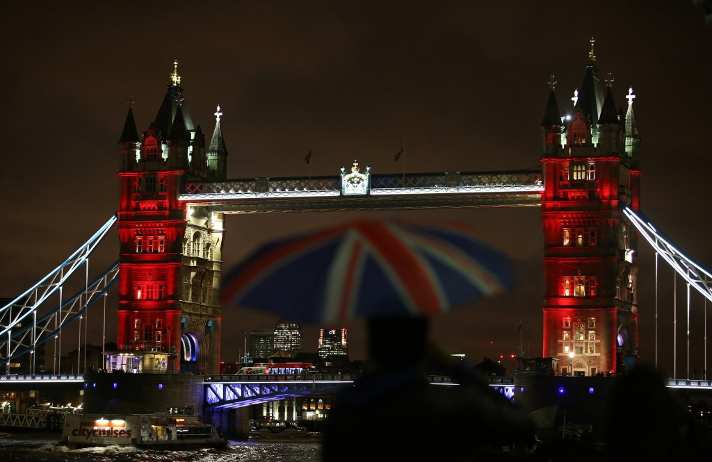 A man shelters from the rain beneath a Union flag-themed umbrella as he photographs London's iconic Tower Bridge, illuminated in blue, white and red lights, resembling the colors of the French national flag, in London on November 14, 2015, as Britons express their solidarity with France following a spate of coordinated attacks that left 128 dead in Paris on November 13. Photo by Justin Tallis/AFP/Getty Images