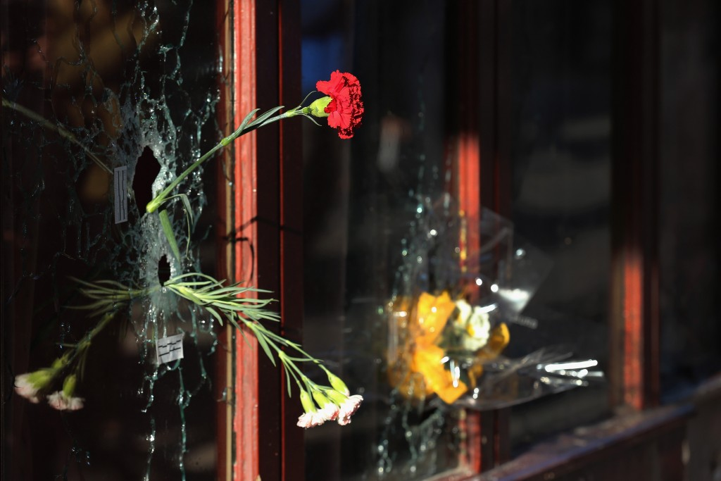A flower is placed inside a bullet hole in the window of Le Carillon restaurant in tribute to the victims of the terror attacks on November 15, 2015 in Paris, France. As France observes three days of national mourning members of the public continue to pay tribute to the victims of Friday's deadly attacks. A special service for the families of the victims and survivors is to be held at Paris's Notre Dame Cathedral later on Sunday. Photo by Christopher Furlong/Getty Images