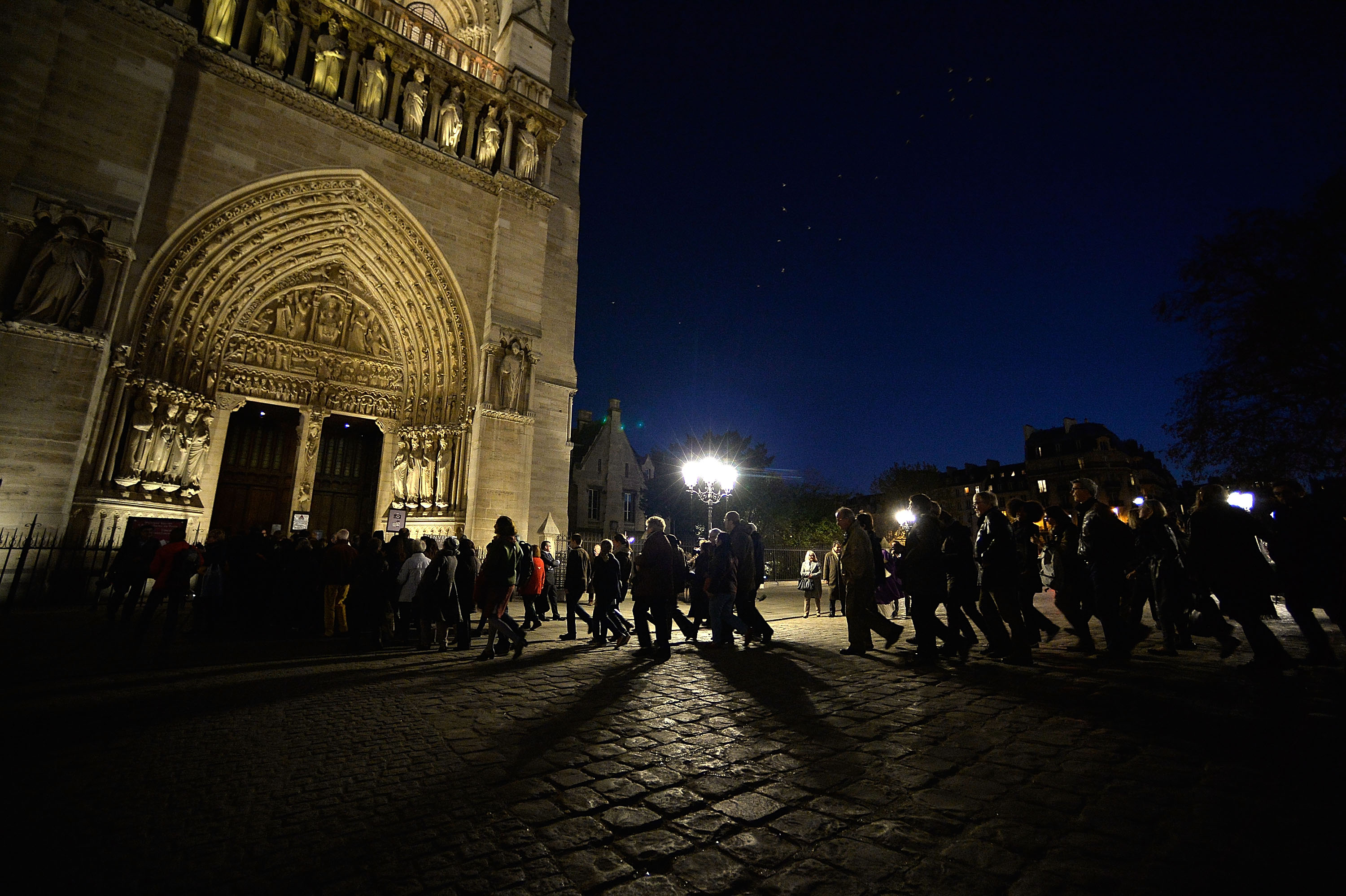 People walk to the Notre Dame Cathedral ahead of a ceremony to the victims of the friday's terrorist attacks on November 15, 2015 in Paris, France. Photo by Pascal Le Segretain/Getty Images