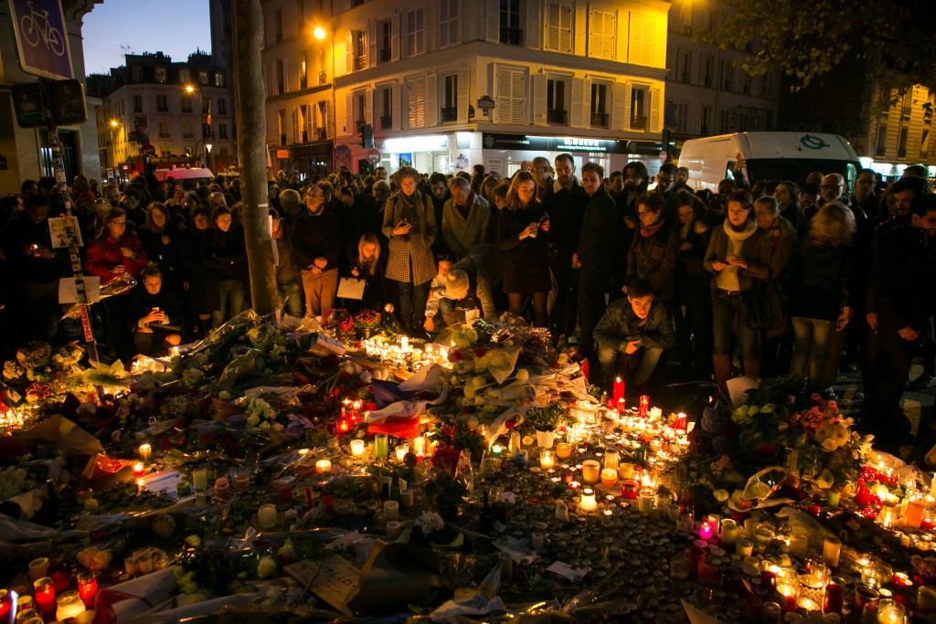 Crowds gather as candles are lit near the Bataclan theatre as France observes three days of national mourning on November 15, 2015 in Paris, France. Photo by Marc Piasecki/Getty Images