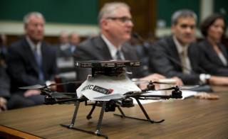 An AscTec Firefly unmanned aerial vehicle (UAV), or drone, sits on the witness table as Joshua Walden, senior vice president at Interl Corp., center, speaks during a House Energy and Commerce subcommittee hearing in Washington, D.C., U.S., on Thursday, Nov. 19, 2015. Photo by Andrew Harrer/Bloomberg via Getty Images.
