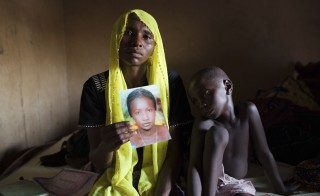 Rachel Daniel holds up a picture of her abducted daughter Rose Daniel, 17, as her son Bukar, 7, sits beside her at her home in Maiduguri, Nigeria, May 21, 2014. Rose was abducted along with more than 200 of her classmates on April 14 by Boko Haram militants from a secondary school in Chibok, Borno state. Boko Haram overtakes ISIL to become the most deadly terrorist group in the world. In 2014, Boko Haram was responsible for more terrorist deaths than any other terrorist organization. Photo by Joe Penney/Reuters