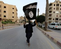 "A member loyal to the Islamic State in Iraq and the Levant (ISIL) waves an ISIL flag in Raqqa June 29, 2014. The offshoot of al Qaeda which has captured swathes of territory in Iraq and Syria has declared itself an Islamic ""Caliphate"" and called on factions worldwide to pledge their allegiance, a statement posted on jihadist websites said on Sunday. The group, previously known as the Islamic State in Iraq and the Levant (ISIL), also known as ISIS, has renamed itself ""Islamic State"" and proclaimed its leader Abu Bakr al-Baghadi as ""Caliph"" - the head of the state, the statement said. REUTERS/Stringer (SYRIA - Tags: POLITICS CIVIL UNREST TPX IMAGES OF THE DAY)  FOR BEST QUALITY IMAGE ALSO SEE: GF2EAAO0VU501 - RTR3WBPT"