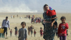 Displaced people from the minority Yazidi sect, fleeing violence from forces loyal to the Islamic State in Sinjar town, walk towards the Syrian border, on the outskirts of Sinjar mountain, near the Syrian border town of Elierbeh of Al-Hasakah Governorate August 11, 2014. Islamic State militants have killed at least 500 members of Iraq's Yazidi ethnic minority during their offensive in the north, Iraq's human rights minister told Reuters on Sunday. The Islamic State, which has declared a caliphate in parts of Iraq and Syria, has prompted tens of thousands of Yazidis and Christians to flee for their lives during their push to within a 30-minute drive of the Kurdish regional capital Arbil. Picture taken August 11, 2014. REUTERS/Rodi Said (IRAQ - Tags: POLITICS CIVIL UNREST TPX IMAGES OF THE DAY) FOR BEST QUALITY IMAGE ALSO SEE: GM1EA8M1B4V01 - RTR424VU