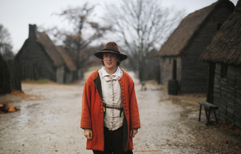 A man playing the role of John Billington stands in the rain in the street at Plimoth Plantation in Plymouth, Massachusetts November 24, 2014.  Plimouth Plantation is a living museum portraying the life of the Native Americans and the English colonists in 1627, seven years after the colonists' arrival.  The three-day harvest festival and feast at the Plimoth Colony in 1621 is the model for the modern-day Thanksgiving holiday in the United States, according to the museum.          REUTERS/Brian Snyder    (UNITED STATES - Tags: SOCIETY TRAVEL) - RTR4FE1V