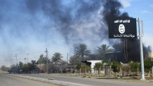 Smoke raises behind an Islamic State flag after Iraqi security forces and Shiite fighters took control of Saadiya in Diyala province from Islamist State militants, November 24, 2014. Iraqi forces said on Sunday they retook two towns north of Baghdad from Islamic State fighters, driving them from strongholds they had held for months and clearing a main road from the capital to Iran. There was no independent confirmation that the army, Shi'ite militia and Kurdish peshmerga forces had completely retaken Jalawla and Saadiya, about 115 km (70 miles) northeast of Baghdad. Many residents fled the violence long ago. At least 23 peshmerga and militia fighters were killed and dozens were wounded in Sunday's fighting, medical and army sources said.  REUTERS/Stringer (IRAQ - Tags: CIVIL UNREST CONFLICT MILITARY TPX IMAGES OF THE DAY) - RTR4FED5