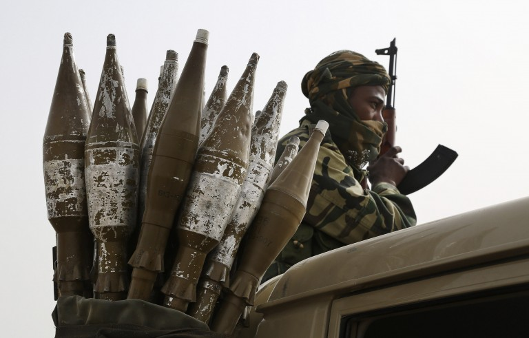 A Chadian soldier rides atop a pickup truck next to a bag of rocket-propelled grenades in Gambaru, Nigeria, February 26, 2015. Niger, Cameroon and Chad have launched a regional military campaign to help Nigeria defeat the Boko Haram insurgency, which aims to carve an Islamic emirate out of northeastern Nigeria. Chad deployed troops last month and is leading efforts to stop repeated cross-border raids by the Islamists, whose operations increasingly threaten Nigeria's neighbours. Picture taken February 26, 2015. REUTERS/Emmanuel Braun (NIGERIA - Tags: POLITICS MILITARY CIVIL UNREST CONFLICT) - RTR4RFAM