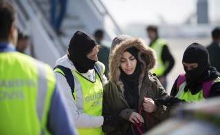 Spanish Civil Guards escorts a Moroccan woman, named as Samira Yerou in a ministry statement, at Barcelona's airport, March 7, 2015. Spanish authorities on Saturday arrested a Moroccan woman resident in Spain on suspicion of attempting to join Islamic State militants in Syria, the interior ministry said. REUTERS/Spanish Interior Ministry/Handout via Reuters (SPAIN - Tags: CIVIL UNREST POLITICS) ATTENTION EDITORS - THIS PICTURE WAS PROVIDED BY A THIRD PARTY. REUTERS IS UNABLE TO INDEPENDENTLY VERIFY THE AUTHENTICITY, CONTENT, LOCATION OR DATE OF THIS IMAGE. FOR EDITORIAL USE ONLY. NOT FOR SALE FOR MARKETING OR ADVERTISING CAMPAIGNS. THIS PICTURE IS DISTRIBUTED EXACTLY AS RECEIVED BY REUTERS, AS A SERVICE TO CLIENTS - RTR4SFVH