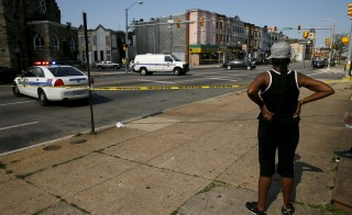 A resident in the neighborhood where Freddie Gray was arrested and where residents rioted over his death in April look on at the scene of a shooting at the intersection of West North Avenue and Druid Hill Avenue in West Baltimore, Maryland May 30, 2015. Local media have reported more than 35 murders in the city of Baltimore since the April rioting over the death of 25-year-old resident Freddie Gray and shootings continue regularly in his West Baltimore neighborhood.  REUTERS/Jim Bourg - RTR4Y6BL