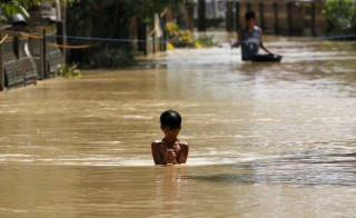 A boy wades through a flooded street in Jaen, Nueva Ecija in northern Philippines October 20, 2015, after the province was hit by Typhoon Koppu. The typhoon swept across the northern Philippines killing at least nine people as trees, power lines and walls were toppled and flood waters spread far from riverbeds, but tens of thousands of people were evacuated in time. REUTERS/Erik De Castro - RTS5CX1