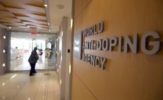 A woman walks into the head office for the World Anti-Doping Agency (WADA) in Montreal, November 9, 2015. An international anti-doping commission recommended on Monday that Russia's Athletics Federation be banned from international competition over widespread doping offences - a move that could see the powerhouse Russian team excluded from next year's Rio Olympics. Russian sports minister said there was no evidence for the accusations against the Federation. REUTERS/Christinne Muschi       TPX IMAGES OF THE DAY      - RTS6766