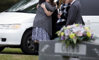 Mourners, believed to be family members, embrace as they gather for the burial of six-year old Jeremy Mardis at a cemetery in Beaumont, Mississippi, November 9, 2015. Mardis, who was autistic, was buckled into the front passenger seat of his father Chris Few's car last week when two Louisiana deputy marshals fired 18 times at the vehicle after chasing it in central Louisiana, state police said.  REUTERS/Lee Celano - RTS680C