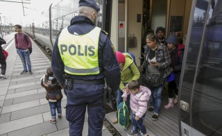 Police gather a group of migrants coming off an incoming train at the Swedish end of the bridge between Sweden and Denmark, in Hyllie district, Malmo November 12, 2015. Sweden will impose temporary border controls from Thursday in response to a record influx of refugees, a turnaround for a country known for its open-door policies that also threw down the gauntlet to other EU nations hit by a migration crisis. REUTERS/Stig-Ake Jonsson/TT News AgencyATTENTION EDITORS - SWEDEN OUT. NO COMMERCIAL OR EDITORIAL SALES IN SWEDEN. THIS IMAGE HAS BEEN SUPPLIED BY A THIRD PARTY. IT IS DISTRIBUTED, EXACTLY AS RECEIVED BY REUTERS, AS A SERVICE TO CLIENTS. NO COMMERCIAL SALES. - RTS6OFE