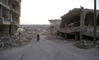A man rides a motorcycle near damaged buildings in Maarat Al-Nouman, south of Idlib, Syria on Sept. 17, 2015. Speaking from Paris on Tuesday, Secretary of State John Kerry said a ceasefire between Syria's government and opposition forces could come in weeks to help end a conflict that has now entered its fifth year. Photo by Khalil Ashawi/Reuters